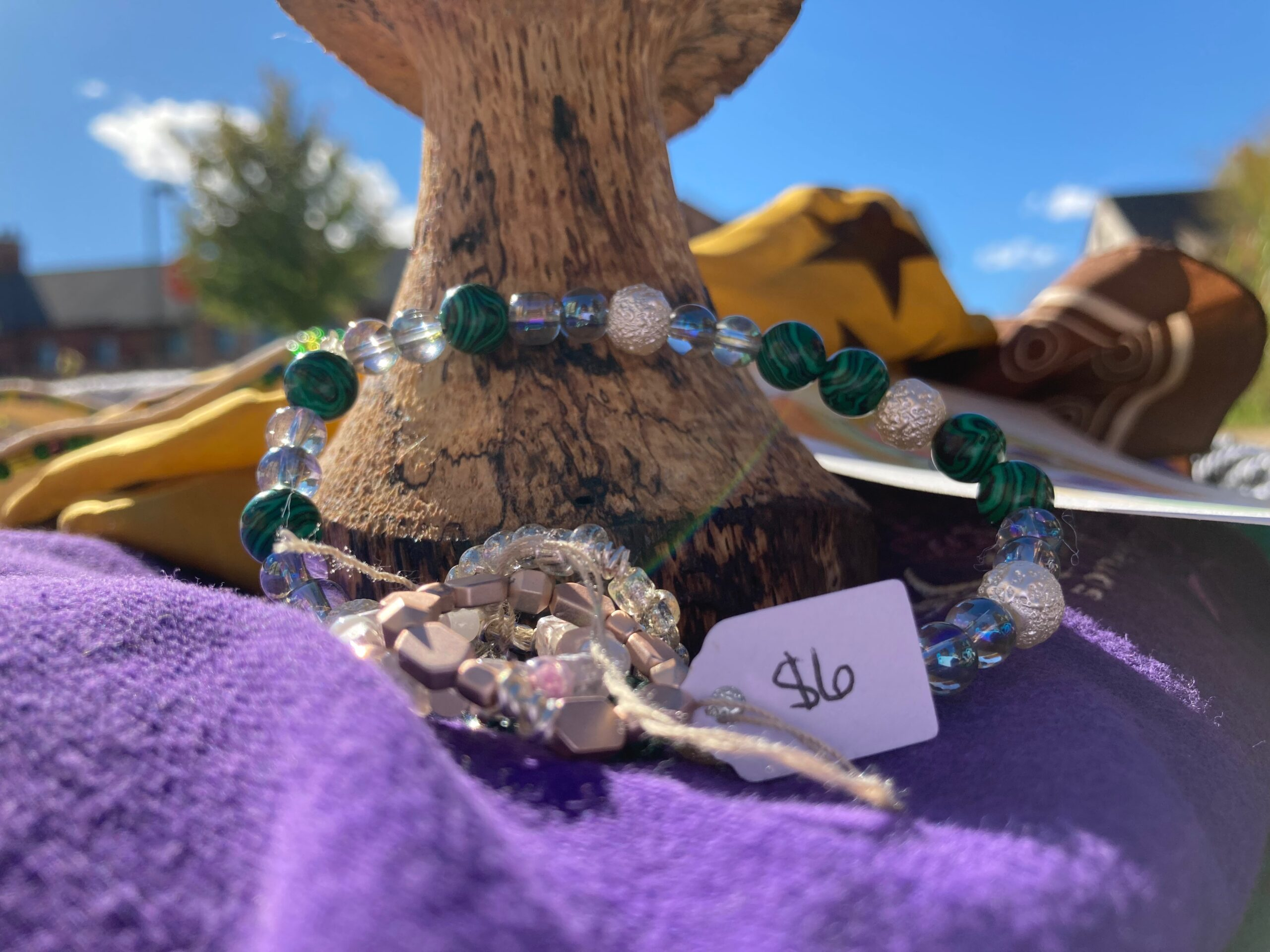 A beaded green, white, and clear bracelet outside.