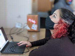 Female student working on laptop looks up