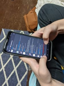 Female student uses phone to chat with others through the app, Discord