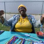 A woman holding up a handmade waist bead