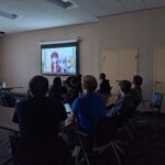 Group of students watch anime on a projector screen