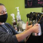 female barista steams milks with espresso machine