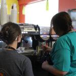 two female baristas steaming milk with espresso machine