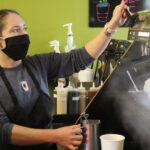 female barista using steam wand on espresso machine